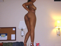 Nasty black bitch posing naked in a room